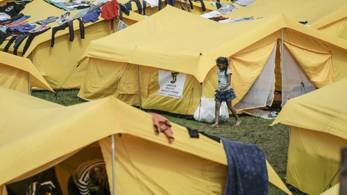 A girl walks in a camp built by the municipal government for homeless Venezuelan migrants in Bogota, Colombia.