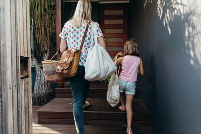 Real life young Australian mum and daughter bring in their groceries in eco shopping bags and basket