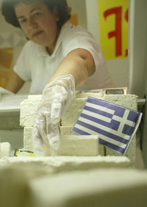 A supermarket worker picks up some feta cheese at a supermarket in central Athens, Greece. In 2005, The European Union's highest court backed Greece's long-running bid to claim exclusive rights to the name of the salty cheese.