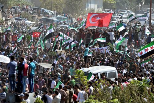 Syrians from the rebel-held northern city of Idlib and its surrounding towns wave the flag of the opposition and chant slogans as they gather for an anti-government demonstration in a main square in Idlib on Friday.