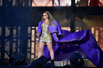 Beyoncé in aDundas purple silk cape and gold embroidered mini dress during her 'On The Run' tour.