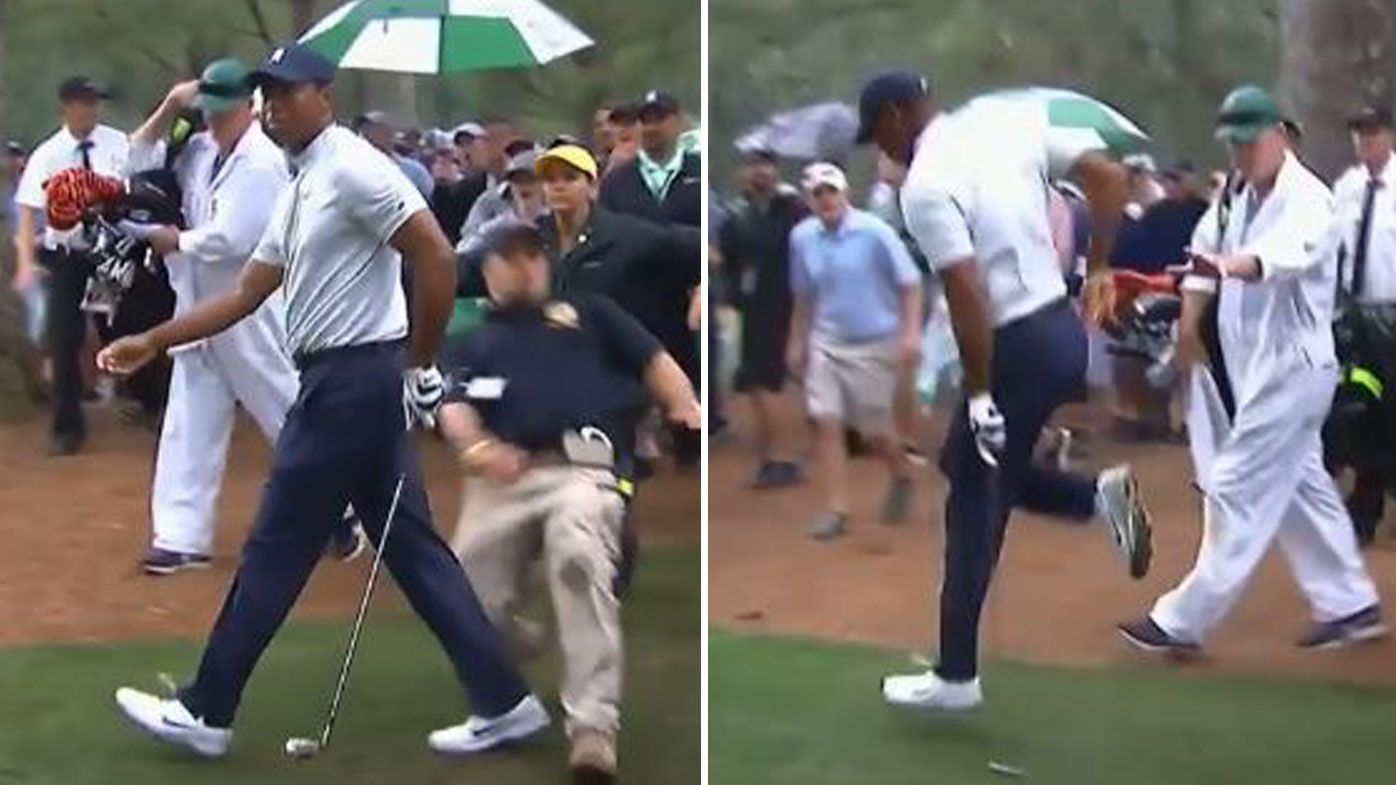 A security guard collides with Tiger Woods during the second round of the Masters.