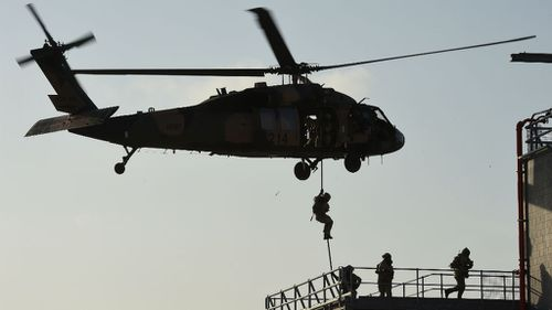 ADF soldiers rappel from a Blackhawk helicopter during a training exercise in Brisbane. (AAP)