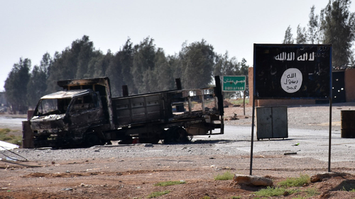 A general view shows a burnt out vehicle next to a banner bearing the Islamic State group's flag in the village of Dibsiafnan on the western outskirts of the Islamist's Syrian bastion of Raqa, after Syrian pro-government forces entered the area on June 11, 2017. George Ourfalian/AFP via Getty Images.