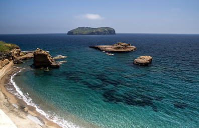 The turquoise rimmed coast of Ventotene, with the island of Santo Stefano in the distance