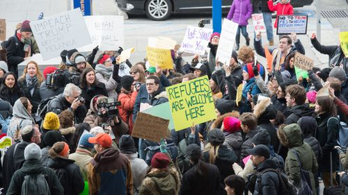 Trump's executive order has sparked protests, with a group gathering outside New York's JFK airport. (AFP)