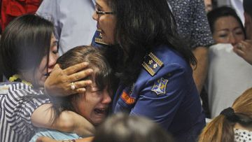 Families of passengers aboard QZ8501 are distraught after seeing the news. (AAP)