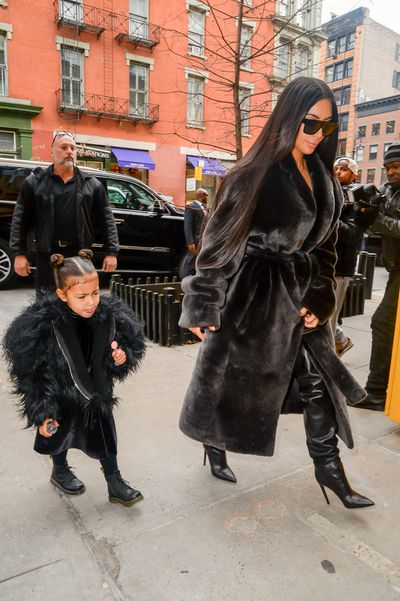 <p>Coat tales: Kim Kardashian West and North West leave their Manhattan hotel in  ebony fur.</p>