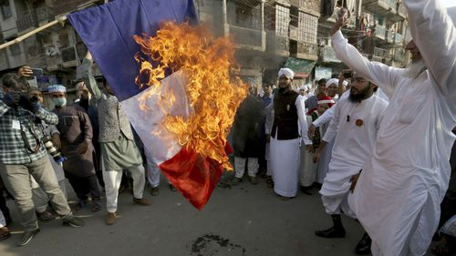 Supporters of religious group burn a representation of a French flag during a rally against French President Emmanuel Macron and republishing of caricatures of the Prophet Muhammad they deem blasphemous, in Karachi, Pakistan, Friday, Oct. 30, 2020