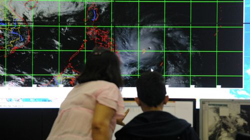 Meteorologists from the Philippine Atmospheric, Geophysical and Astronomical Services Administration (PAGASA) monitor and plot the direction of super typhoon Hagupit. (Getty Images)