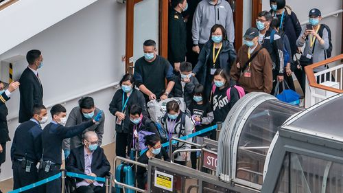 Passengers line up to leave the World Dream cruise ship at Kai Tak Cruise Terminal on February 9, 2020 in Hong Kong, China. 3,600 passengers and crew members quarantined on World Dream cruise ship are finally allowed to disembark after all 1,800 crew members test negative for coronavirus as vessel has been docked at Kai Tak Cruise Terminal for more than four days.