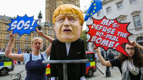 A man is seen dressed as British Prime Minister Boris Johnson pushing the plunger on a 'No-Deal Bomb' while demonstrating in central London.