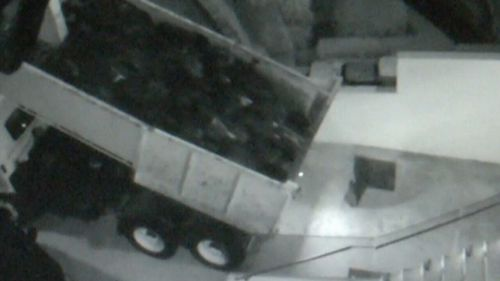 A large truck has been caught on camera dumping a large pile of waste potentially containing asbestos on the driveway of a family home in Sydney's north-west. (9NEWS)