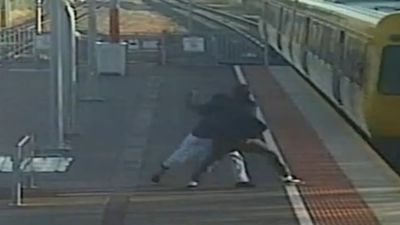 Man tries to shove teen girlfriend in front of train