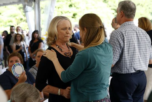 Judy Hiaasen, left, sister of Rob Hiaasen, one of the journalists killed in the shooting at The Capital Gazette newspaper offices, speaks with a mourner during a memorial service (AP Photo/Patrick Semansky)
