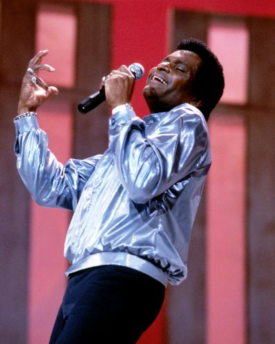 Charley Pride, US Country music singer, wearing a silver jacket and holding a microphone during a live concert performance, circa 1975.
