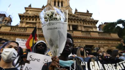 A man holds up a bunch of flowers at Sydney's Black Lives Matter protest.
