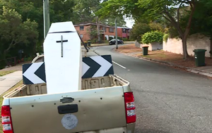 Brisbane residents divided over coffin street prop, a grim reminder to drivers to slow down