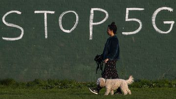 A woman in England walks past an anti-5G graffiti message.