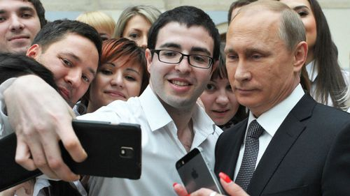 Russian President Vladimir Putin (R) poses for a picture with call-centre employees. (AAP)