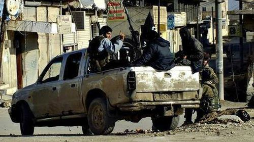 Fighters from the al-Qaeda linked Islamic State of Iraq and the Levant (ISIL) patrolling in Raqqa, Syria. (AAP)