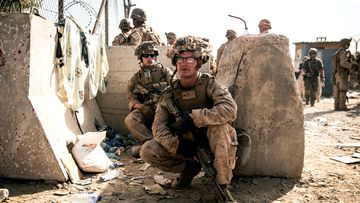 US Marines take a moment to rest during an evacuation at Hamid Karzai International Airport in Kabul, Afghanistan.
