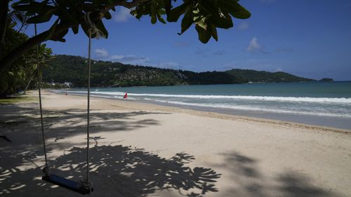 An empty swing hangs from a tree on the empty tourist beach of Patong on Phuket, southern Thailand.