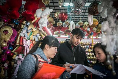 A foreign buyer shops for Christmas decorations in a store at a wholesale market in Yiwu city.