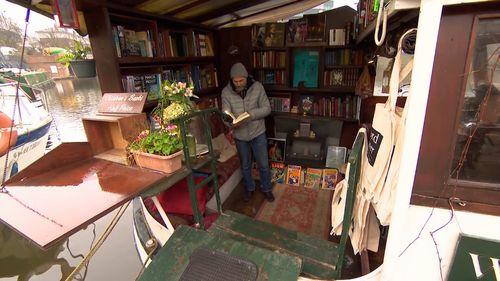 Jon Privett inside his floating bookstore. (9NEWS)