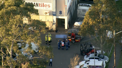 A man has died after being crushed by a semi-trailer.