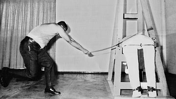 A caning officer demonstrates on the device used to cane criminals in Singapore.