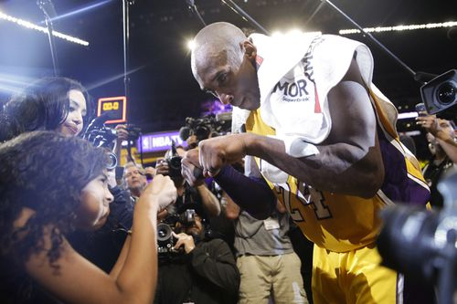 Los Angeles Lakers' Kobe Bryant fist-bumps his daughter Gianna after the last NBA basketball game of his career, in 2016.