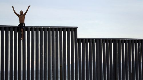 A member of the migrant caravan sits atop the border wall between the United States and Mexico.