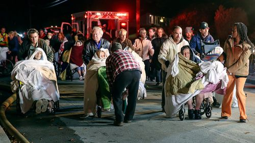 Residents are gathered near the scene after being evacuated. (AAP)