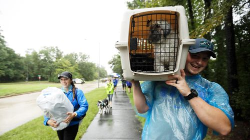 Jessie Rall carries his pets as he walks with his wife Montana Roll after being rescued by boat from their home among floodwaters from Tropical Storm Harvey. (AAP)