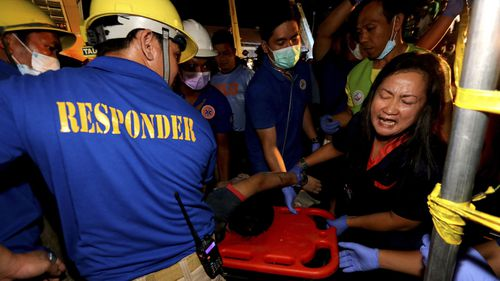 Emergency responders carry out an earthquake victim from a commercial building in Porac town, Pampanga Province, north of Manila, Philippines.