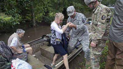 Members of the Louisiana Army National Guard rescue people from rising flood water near Walker. (AP)