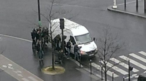Police huddle behind a van in east Paris where another hostage situation is unfolding.