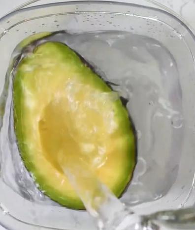 Perfectly ripe avocado cut in half water
