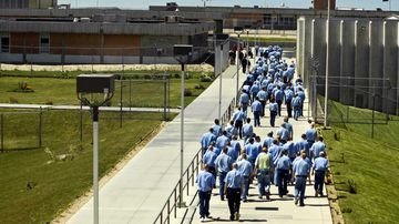 Inmates walk to the dining hall from their cell block at the Idaho State Correctional Institution outside Boise, Idaho.  (AAP)