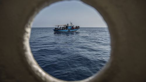 A migrants boat is seen though a porthole before being rescued by the Open Arms aid boat on Sunday June 30, 2019
