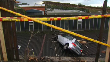 a car is perched on a Leichhardt roof after crashing through a neighbouring fence this afternoon.
