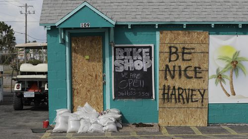 """A sign reading """"Be Nice Harvey"""" was left behind on a boarded up business, (AAP)"""