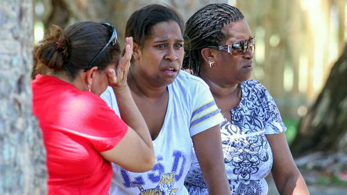 Three women, believed to be relatives of the victims, near the scene of the crime. (AAP)