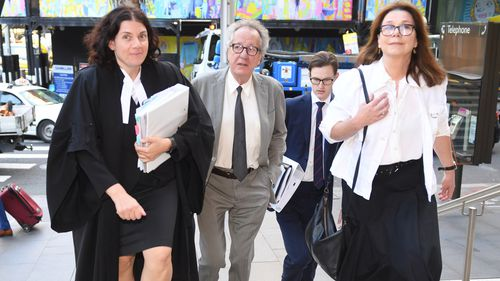 Australian actor Geoffrey Rush (centre) arrives at the Federal Court in Sydney, Wednesday, October, 31, 2018.