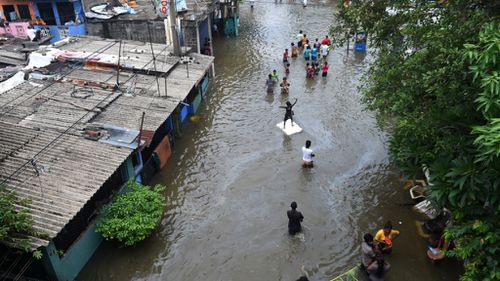 Colombo residents wade through floodwaters. (AFP)