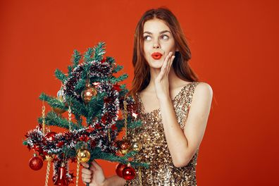 Woman in a Christmas dress with a Christmas tree in her hands