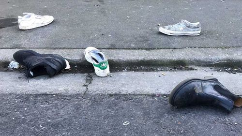 Stray shoes litter the gutter outside the Dunedin home where a student was crushed to death.