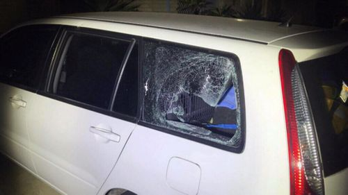 The window of a car in the driveway was smashed.