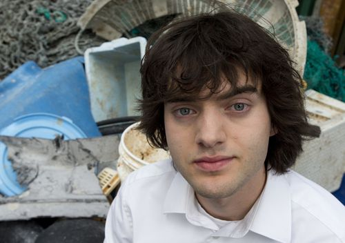 Dutch innovator Boyan Slat poses for a portrait next to a pile of plastic garbage prior to a press conference in Utrecht, Netherlands.